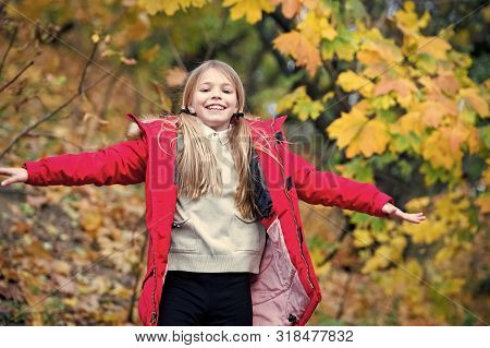 Free And Happy Cutie. Child Blonde Long Hair Walking In Warm Jacket Outdoor. Girl Happy In Red Coat