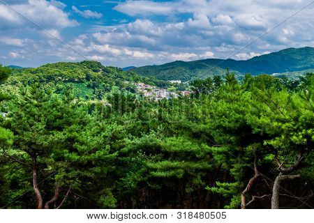 Landscape of city in mountain valley under beautiful blue sky full of low level puffy white clouds. poster