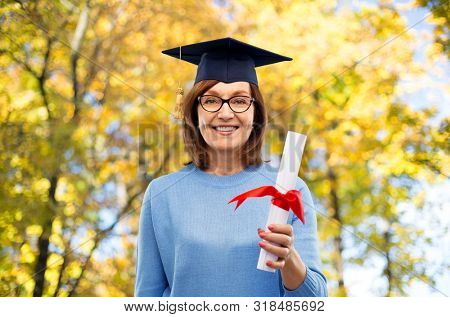 graduation, education and old people concept - happy senior graduate student woman in mortar board with diploma laughing over autumn park background