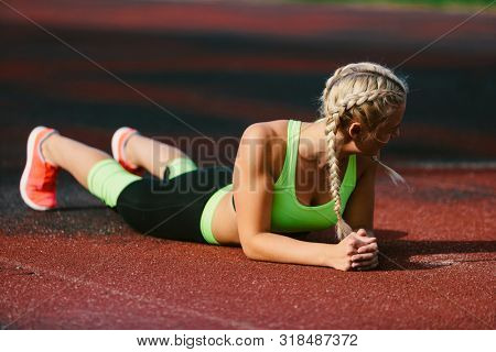 young caucasian fitness woman resting at stadium
