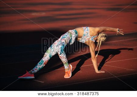 young caucasian fitness woman is stretching at stadium on a sunny day