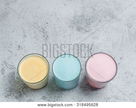Trendy Drinks: Blue, Yellow And Pink Latte. Top View Of Hot Butterfly Pea Or Blue Spirulina Latte, Y