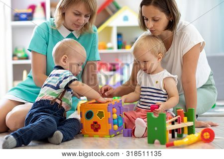 Group Of Babies Play Together With Mothers In The Classroom In Nursery Or Preschool
