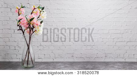 Glass Pot Of Dried Cherry Blossom On White Brick Wall Texture Background, Copy Space.