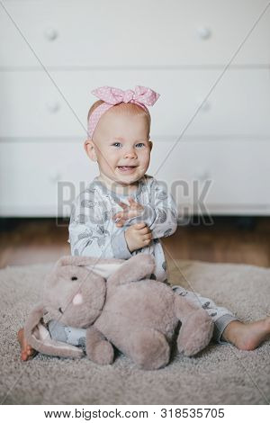 Little Cute Baby Girl Sitting On A Floor In A Room With Adorable Plush Soft Toy Rabbit