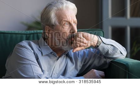 Pensive Thoughtful Senior Man Looking Away Sitting Alone At Home