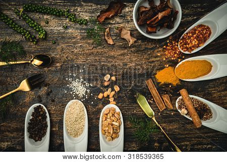 Various Colorful Herbs And Spices On Wooden Table. Top View Of Spices And Herbs. Spices And Herbs Ov