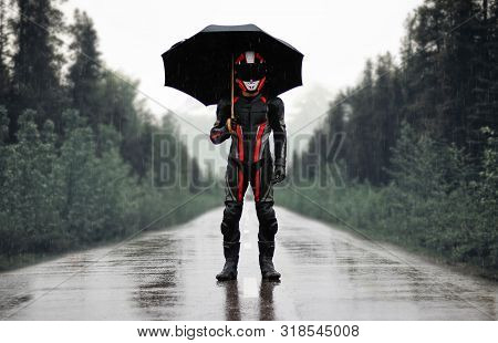 Motorcyclist In Full Gear And Helmet With Umbrella In The Rain. Motorcyclist In The Dark Woods.