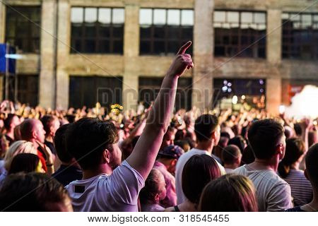 Concert Crowd Attending A Concert, People Silhouettes Are Visible, Backlit By Stage Lights. Raised H