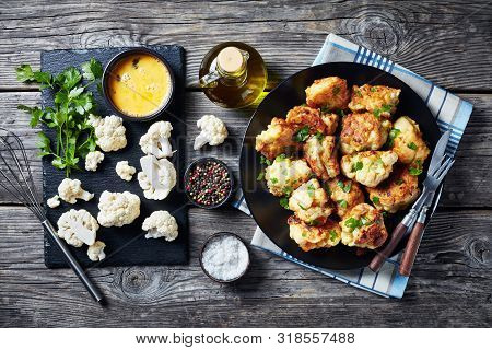 Moroccan Tempura-style Fried Cauliflower Florets Served On A Black Plate On An Old Wooden Table With