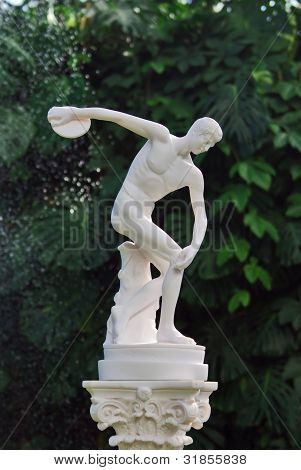 The sculpture of discobolus in park over green leaves poster