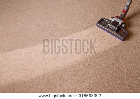 Housekeeper Doing Vacuum Cleaning. Maid Vacuuming The Carpet. Carpet Is Dirty With Cleaned Area.