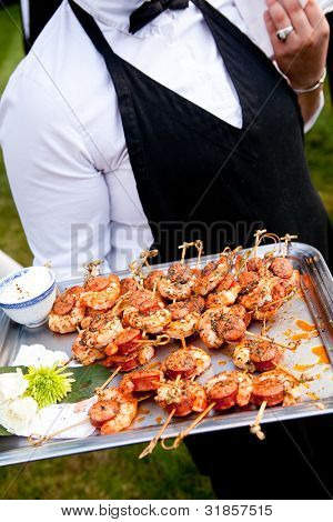 a waiter serving shrimp appetizers during a catered event