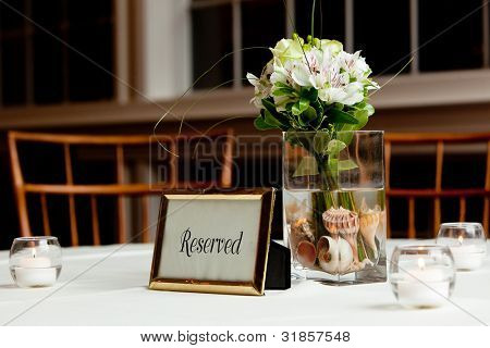 a wedding bouquet in a vase filled with water and sea shells on a reserved table