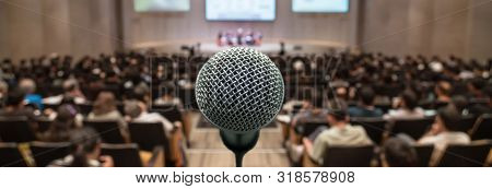 Banner And Web Page Or Cover Template Of Microphone Over The Abstract Blurred Photo Of Conference Ha