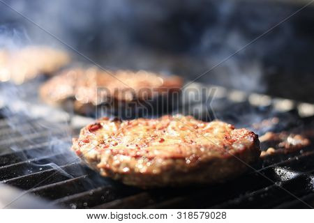 Burgers. Hamburgers Being Flame Broiled On The Gas Grill