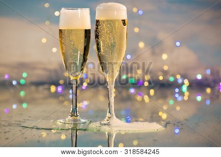 Yellow And Bubbly Champagne Served In Two Glass Cups Against A Background Illuminated By Many Colour