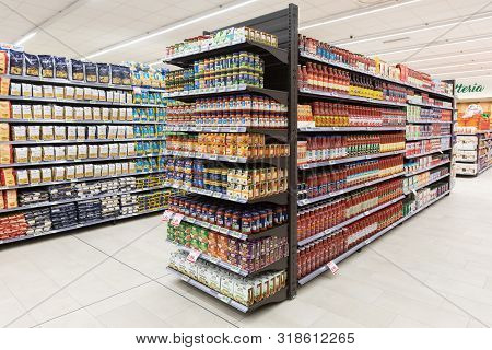Rome / Italy. December 05, 2018: Lanes Of Shelves With Goods Products Inside A Ma Supermarket In Ita