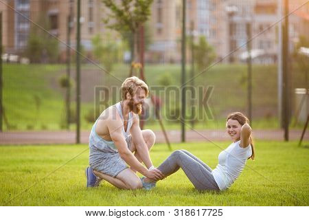 Sit Ups Fitness Couple Exercising Sit Up Outside In Grass. Fit People Working Out Cross Training. Wo