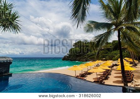 Umbrella From The Sun, Beach Beds, Infinity Pool, Under Palm Trees On A Small Sandy Beach On A Tropi