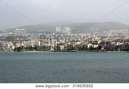 The Coastline Of The City Of Kusadasi, Turkey As Seen Across The Water On A Hazy Foggy Day.