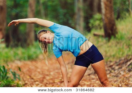 Young Woman Stretching after a Run in the Forest