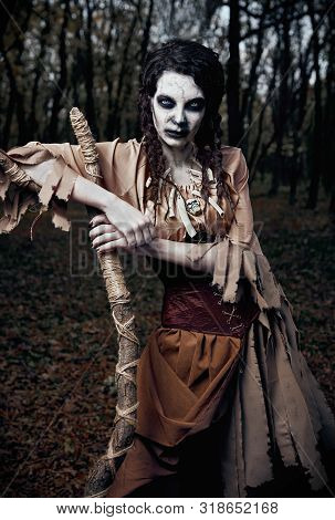 Halloween Theme: Wicked Scary Voodoo Witch With Staff. Portrait Of The Evil Sorceress In Dark Grove.