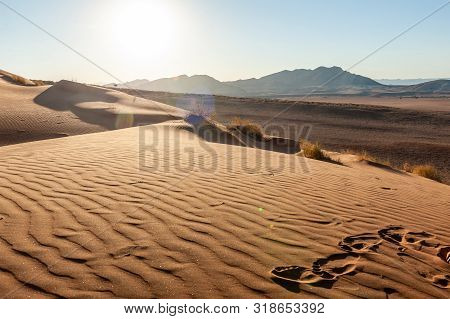 The Rising Sun Is Casting Long Shadows Across The Dune Landscape Of The Khomas Region In Central Wes