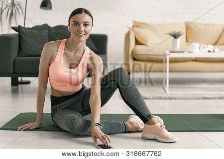 Female Exercising With Cell Phone At Home Stock Photo