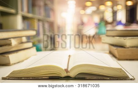 Open Textbooks On Reading Desk In Blurred Library Room Background
