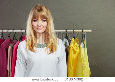 Pretty Happy Woman With Clothing From Wardrobe. Young Undecided Shopper Girl Bought New Clothes. Sho