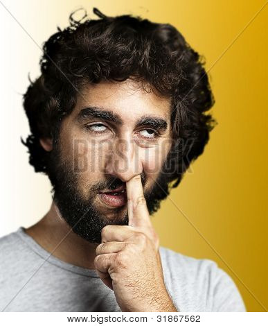 young man with the finger in his nose over yellow background