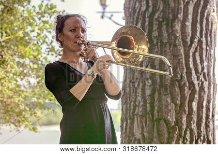 Girl Learning To Play Trombone. Girl Plays Standing On The Alley Of A City Park.