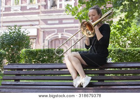 Girl Learning To Play Trombone. Girl Plays Sitting On A Park Bench.