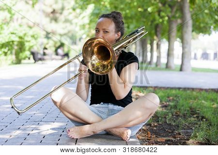 Girl Learning To Play Trombone. Girl Plays Sitting On The Plates Of A Park Alley.