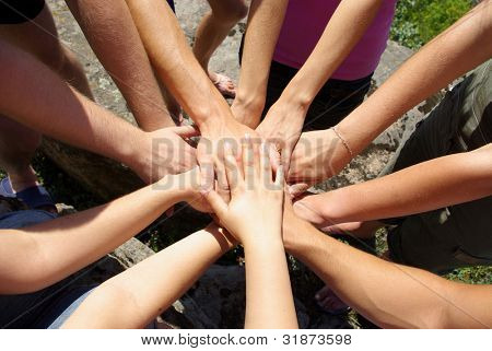 Hands of of diverse group of friends