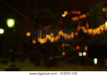 Defocused Night City Life People And Street Lamps. Bokeh Urban City Background Effect. Holidays, Sal
