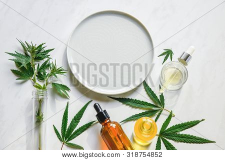Various Glass Bottles With Cbd Oil, Thc Tincture And Hemp Leaves On A Marble Background. Copy Space,