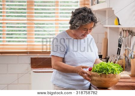 Asain Senior Woman Preparing Vegetables  Salad In The Kitchen. Healthy Meal Concept.aging At Home