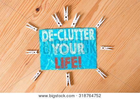 Word writing text De Clutter Your Life. Business concept for remove unnecessary items from untidy or overcrowded places Colored clothespin papers empty reminder wooden floor background office. poster