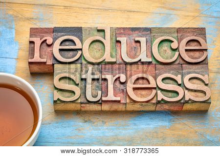 reduce stress - word abstract in letterpress wood type with a cup of tea