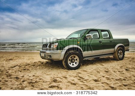 Stegna / Poland - August 1 2019: Green Pick-up Truck Parked On The Sandy Beach With Sea, Blue Sky An