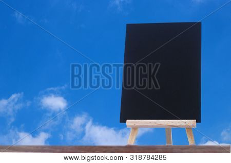 Image Of Empty Small Chalkboard On Wooden Easel For Notes With Sky Background. Mock-up Of Menu Black