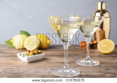 Glasses Of Lemon Drop Martini Cocktail With Zest On Wooden Table Against Grey Background