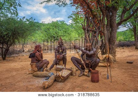Opuwo, Namibia - March 31, 2019: People Of The Himba Tribe Sitting And Making Their Tools. The Himba