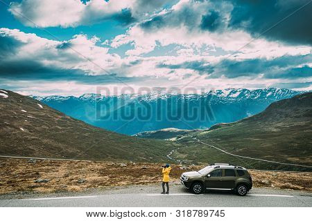Aurlandsfjellet, Norway. Young Caucasian Woman Lady Tourist Traveler Photographer Taking Pictures Ph