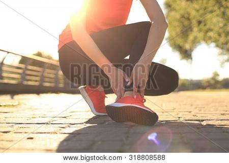 Sport Woman - Runner Holding Painful Sprained Ankle In Pain. Female Athlete With Joint Or Muscle Sor
