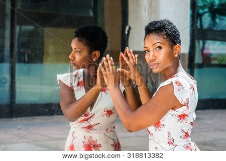 Young African American Woman With Short Afro Hairstyle, Standing By Mirror In New York, Hands Touchi