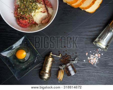 Minced Meat, Bread Slices, Spices, Pepper, Egg On Wood Background, Empty Space. Prepared Ingredients