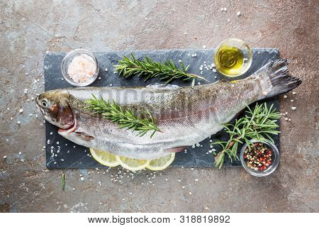 Raw Trout Fish On Slate With Rosemary And Lemon On A Stone Table, Top View